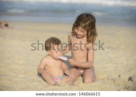 Kids eating icecream on the beach, big sister helping her small baby sister - stock photo