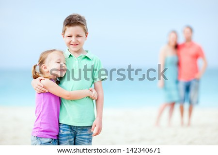 Kids embracing each other while parents standing on background - stock photo