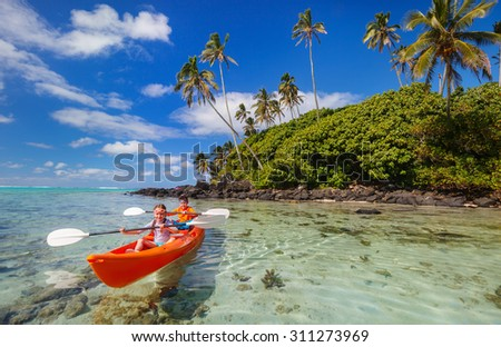 Kids enjoying paddling in colorful red kayak at tropical ocean water during summer vacation - stock photo