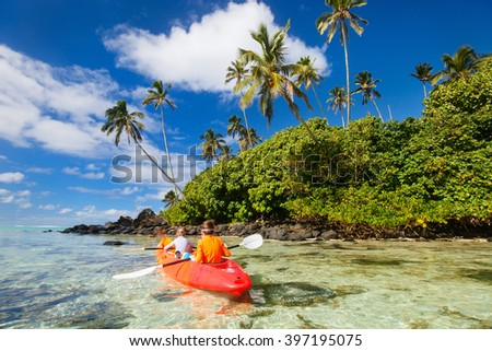 Kids enjoying paddling in colorful red kayak at tropical ocean water during summer vacation in South Pacific - stock photo