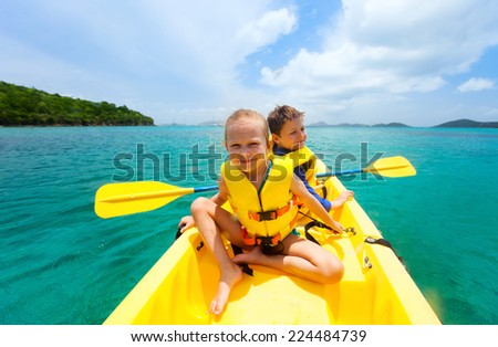 Kids enjoying paddling in colorful yellow kayak at tropical ocean water during summer vacation - stock photo