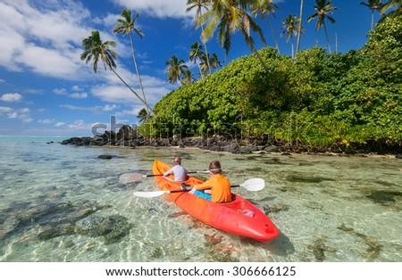 Kids enjoying paddling in colorful yellow kayak at tropical ocean water during summer vacation - stock photo