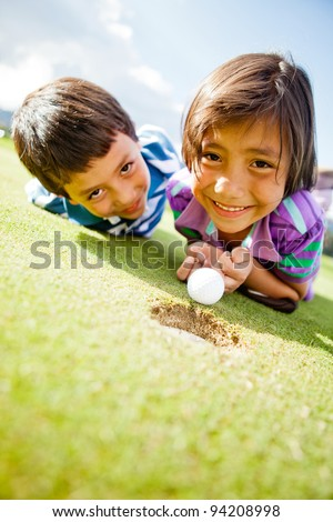 Kids enjoying playing golf lying on the field and smiling - stock photo