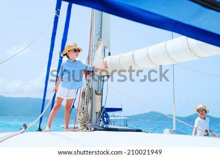 Kids enjoying sailing on a luxury catamaran or yacht - stock photo