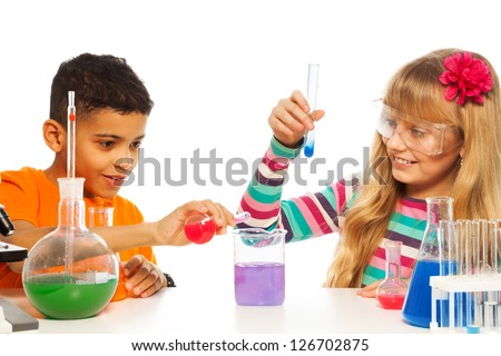 Kids experimenting with chemistry in the school chemistry laboratory class - stock photo