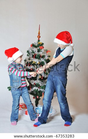 Kids fight because of decoration on Christmas tree - stock photo