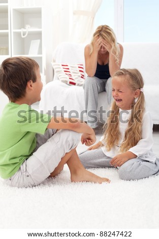 Kids fighting and crying with desperate mother in the background - stock photo
