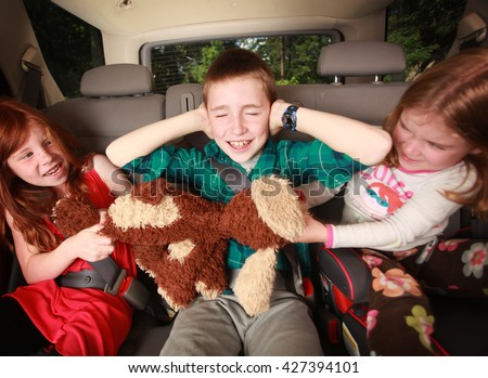 Kids fighting in the backseat of a car - stock photo