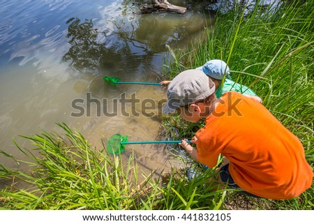 Kids fishing with nest in a lake