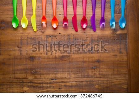 Kids funny eating. Composition of Colorful cutlery on wooden table - stock photo