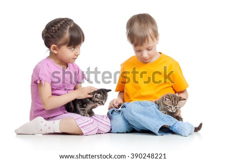 Kids girl and boy sitting on the floor, playing with small kittens - isolated
