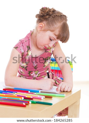 Kids,girl,kid,child- Cute little girl draws with markers while sitting at table. Isolated on white. - stock photo