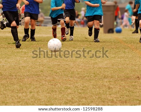 Kids going after the soccer ball in a game. - stock photo