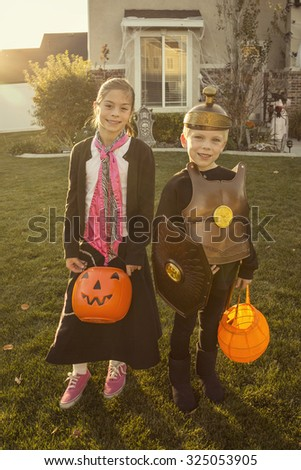 Kids Going Trick or Treating on Halloween Night. Children in costumes standing in front of a decorated home holding their candy bags - stock photo