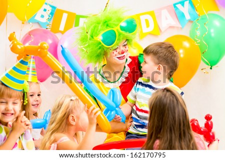 kids group and clown celebrating birthday party