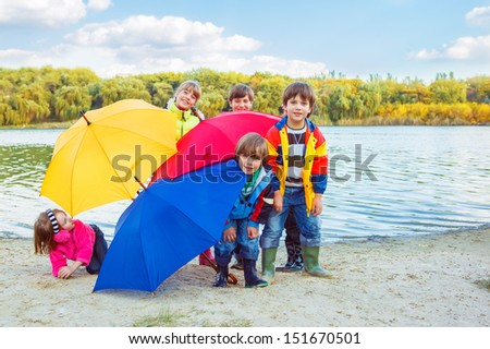 Kids group hiding behind umbrellas - stock photo