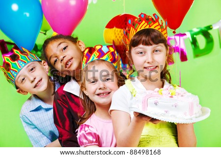 Kids group in party crowns holding birthday cake - stock photo