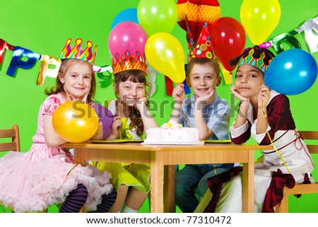 Kids group sitting at the table with the birthday cake - stock photo
