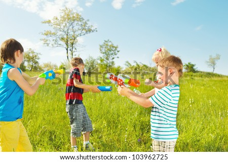 Kids group with water guns and soakers shooting - stock photo