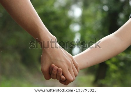 kids hand by hand in the green path - stock photo