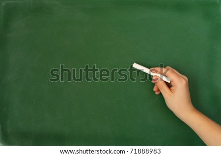 kids hand holding a white chalk about to write