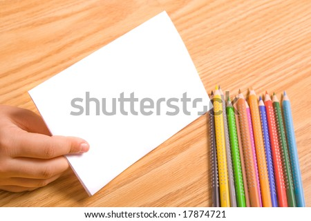 Kids hand holding blank paper for message. Copy space - stock photo