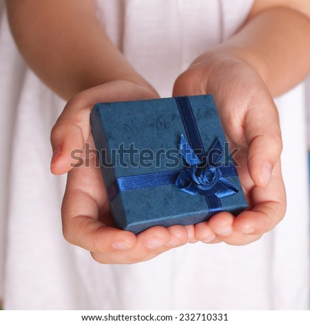 Kids hands holding a gift close-up. New Year, Christmas, holiday concept. - stock photo