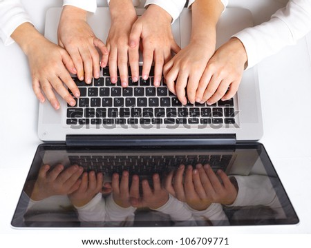 Kids hands on keypad of laptop at workplace - stock photo