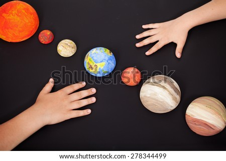 Kids hands with the planets of the solar system - science home project, focus on Earth - stock photo