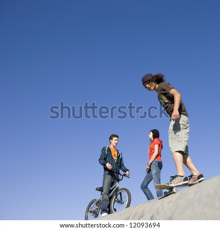 Kids hang out and do tricks at the skatepark - stock photo