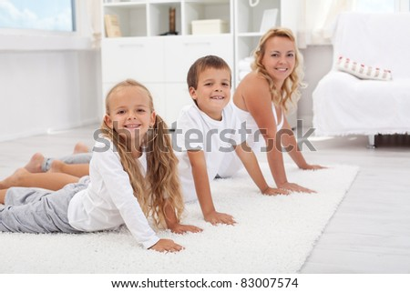 Kids having fum doing some morning gymnastic with their mother at home - focus on the little girl