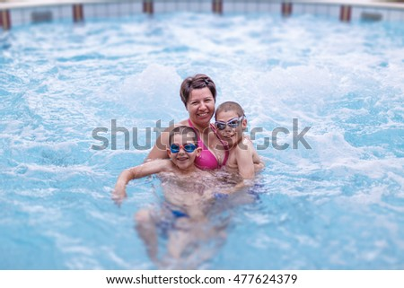 Kids having fun and laughing with happy smiling mother in swimming pool