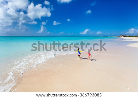 Kids having fun at tropical beach during summer vacation playing together at shallow water