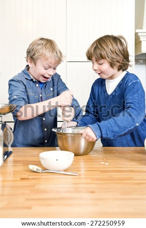 Kids having fun during a baking workshop, whisking dough in a stainless steel bowl during a birthday party - stock photo