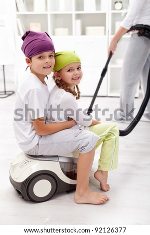 Kids having fun helping their mother cleaning the room