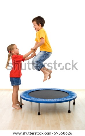 Kids having fun on a trampoline in the gym - helping each other - isolated - stock photo
