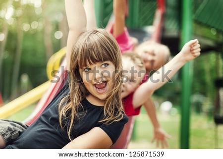 Kids having fun on slide - stock photo