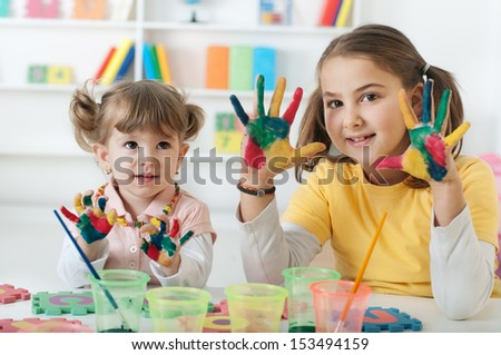 Kids having fun painting with watercolors - stock photo