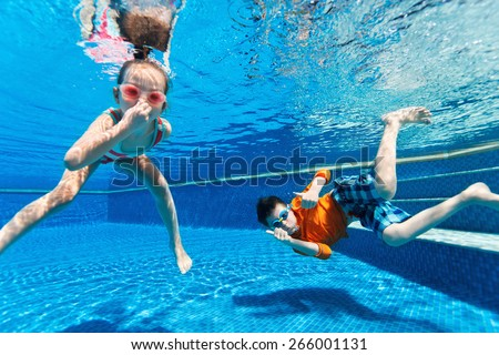 Kids having fun playing underwater in swimming pool on summer vacation - stock photo