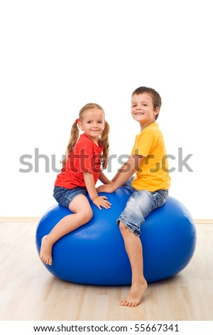Kids having fun playing with a large gymnastic exercise ball - isolated - stock photo