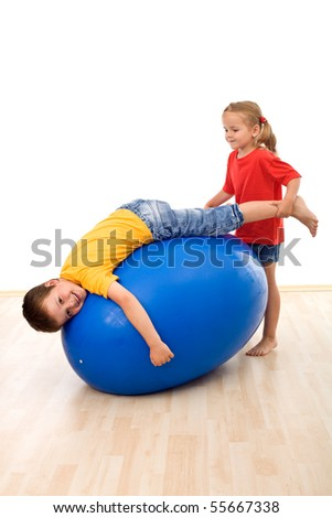 Kids having fun playing with a large rubber exercise ball - stock photo