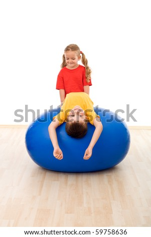 Kids having fun with large exercise ball in the gym - isolated - stock photo