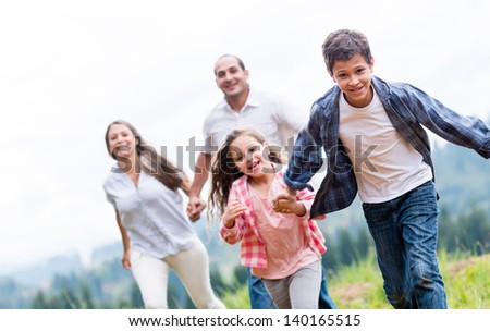 Kids having fun with their family outdoors - stock photo