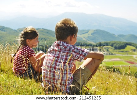Kids hiking in the mountains in Italy.  Little girl and boy sitting on the grass and looking at the Italian mountains. - stock photo