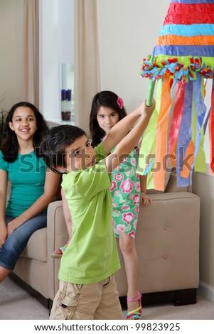 Kids hitting a pinata at birthday party - stock photo