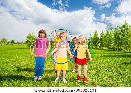 Kids hold hula hoops during exercising activity - stock photo