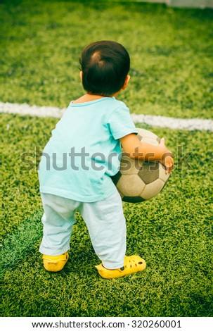 kids holding ball on football grass. - stock photo