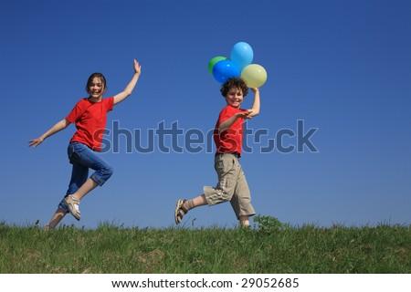 Kids holding balloons, running against blue sky - stock photo