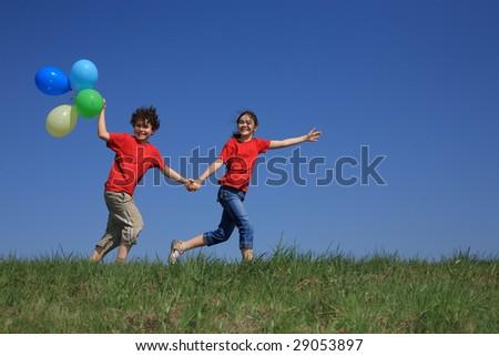 Kids holding balloons running outdoor - stock photo