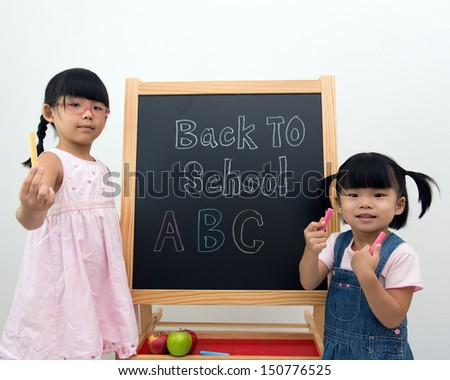 Kids holding chalks standing in front of the blackboard - stock photo